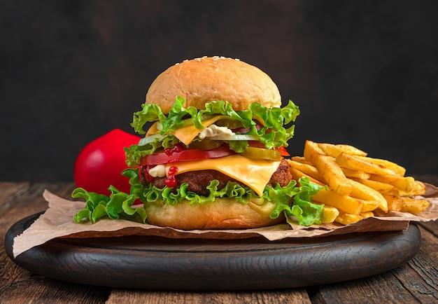 Saftiger, köstlicher burger und pommes frites an einer braunen wand mit platz zum kopieren. fastfood.