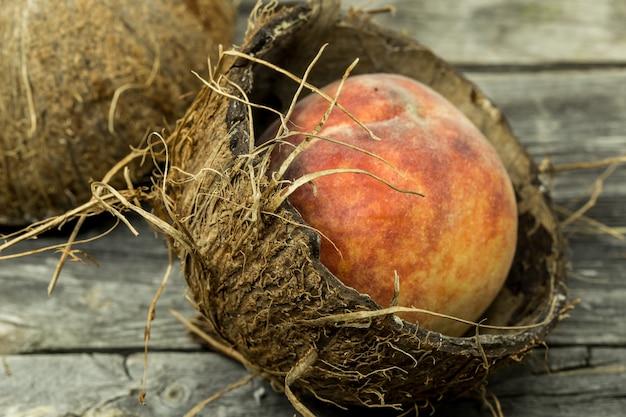 Saftiger pfirsich in kokosnussschale auf holztisch