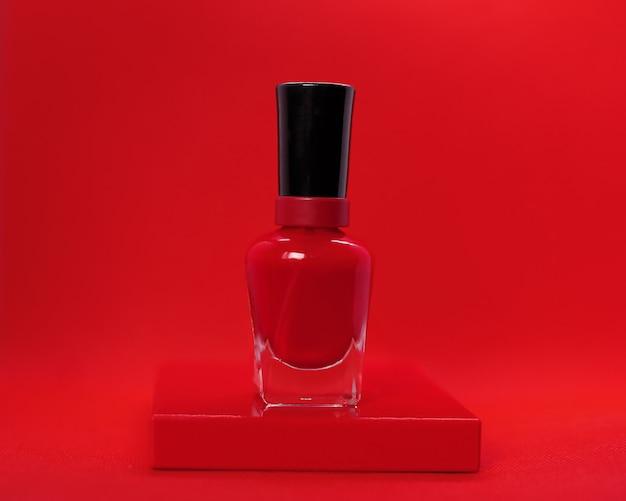 Saftiger roter nagellack auf dem roten hintergrund. das konzept der handpflege, werbung maniküre salon, hersteller von nagellacken, schönen nägeln, kosmetik. nahaufnahmefoto.