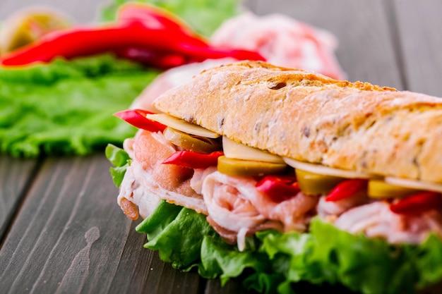 Saftiger roter pfeffer schaut aus unter vollkornbrot im sandwich