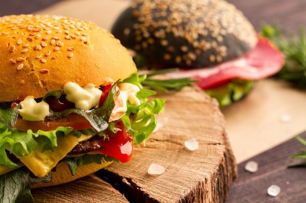 Saftiger ungesunder fast-food-burger mit rindfleisch, cheddar-käse, emmentaler, salat