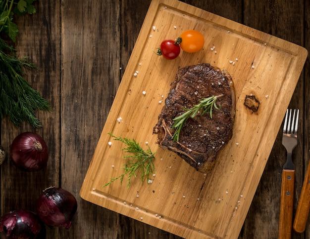 Saftiges fleisch geschmückt mit tomaten und zwiebeln auf holzhintergrund, ansicht von oben