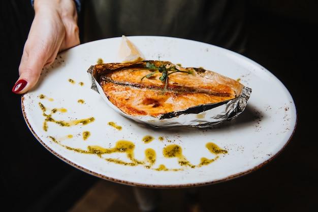 Saftiges gebackenes fischsteak auf einer ronde