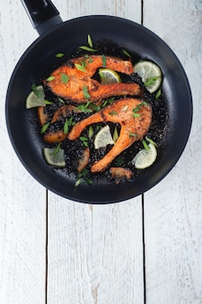 Saftiges gegrilltes lachssteak mit zitrone, gewürzen und limette in einer pfanne auf einem hellen holztisch. köstlich gekochtes lachsfilet