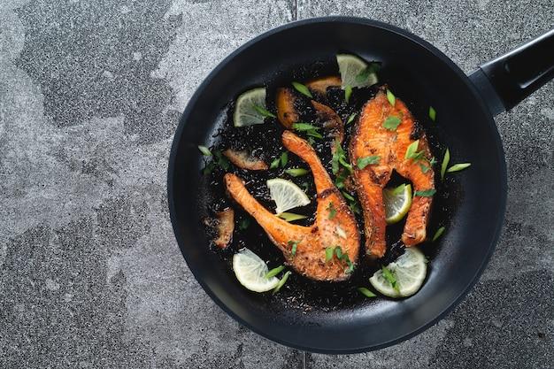 Saftiges gegrilltes lachssteak mit zitrone, gewürzen und limette in einer pfanne auf einem naturschiefersteintisch, nahaufnahme. köstlich gekochtes lachsfilet