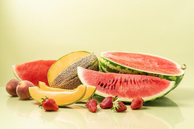 Saftiges reifes frisches stück wassermelone und melone cantaloupe pfirsiche und erdbeeren