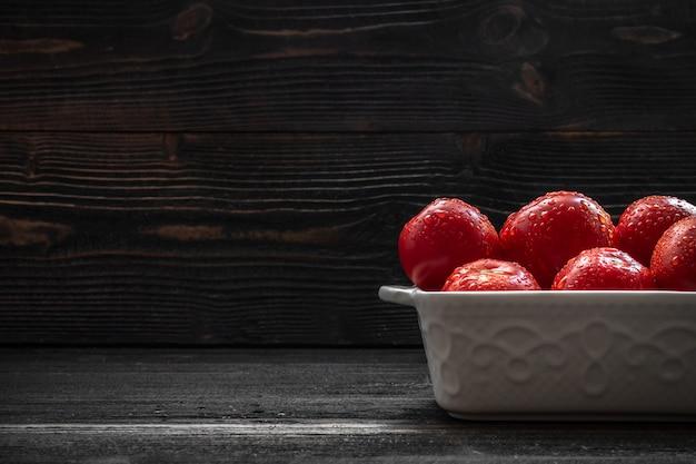 Saftiges rotes tomatenstillleben auf dunklem hintergrund