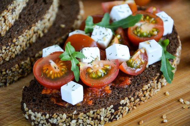 Saftiges sandwich mit tomate, käse und kräutern auf schwarzbrot mit getreide