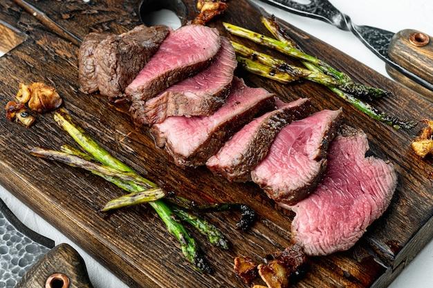 Saftiges steak medium rare beef filet mignon oder eye filet set, mit zwiebel und spargel, auf holzbrett, mit fleischmesser und gabel, auf weißem steinhintergrund