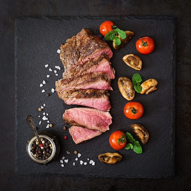 Saftiges steak mit seltenem rindfleisch mit gewürzen und gegrilltem gemüse. draufsicht