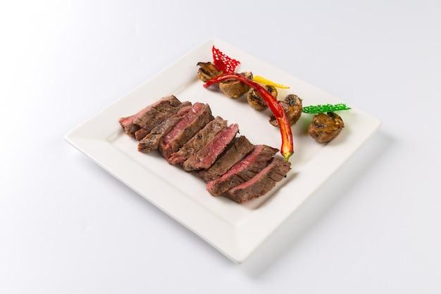 Saftiges steak mittelrares rindfleisch mit gewürzen und gegrilltem gemüse