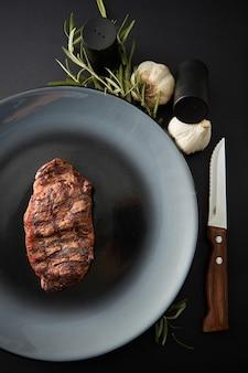 Saftiges steak mittleres seltenes rindfleisch mit gewürzen auf dunklem tisch