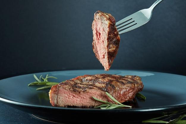 Saftiges steak mittleres seltenes rindfleisch mit gewürzen und einem stück fleisch auf einer gabel