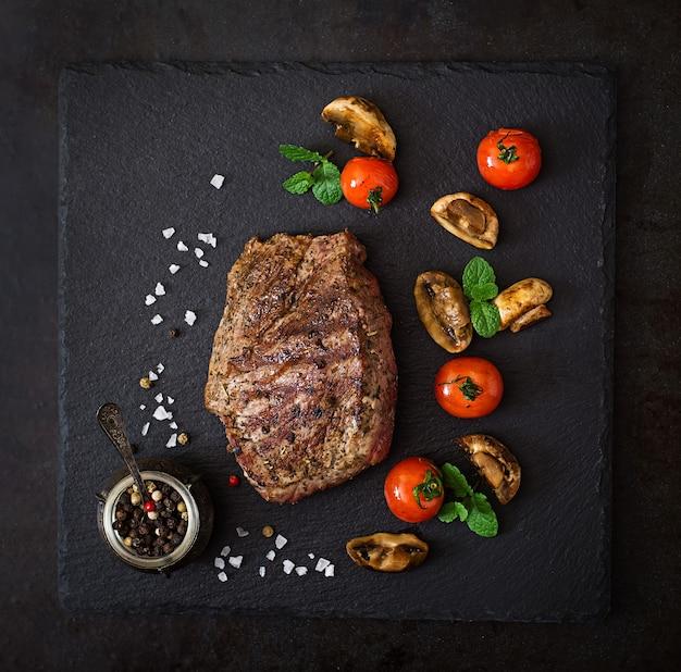 Saftiges steak mittleres seltenes rindfleisch mit gewürzen und gegrilltem gemüse.