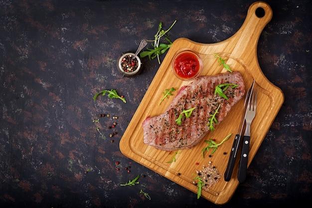 Saftiges steak seltenes rindfleisch mit gewürzen auf einem holzbrett. draufsicht. flach legen.