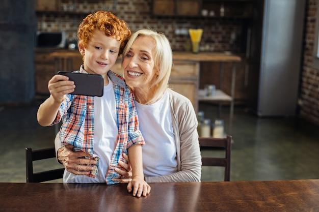 Sag cheese. liebevolle großmutter, die ihren lockigen enkel umarmt, der auf einem stuhl steht, während beide in die kamera eines smartphones lächeln und zusammen ein selbstporträt machen.