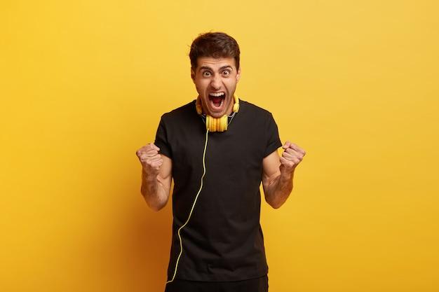 Sag ja zu großartigem sound. überglücklicher emotionaler junger kaukasischer mann ballt die fäuste, schreit laut und trägt ein schwarzes t-shirt
