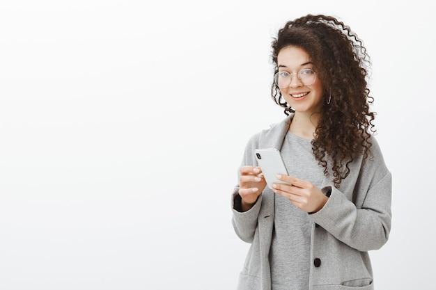 Sag mir deine telefonnummer. porträt einer stilvollen, gut aussehenden, selbstbewussten frau in einer trendigen brille und einem grauen mantel, die ein smartphone hält und mit interesse und freude blickt