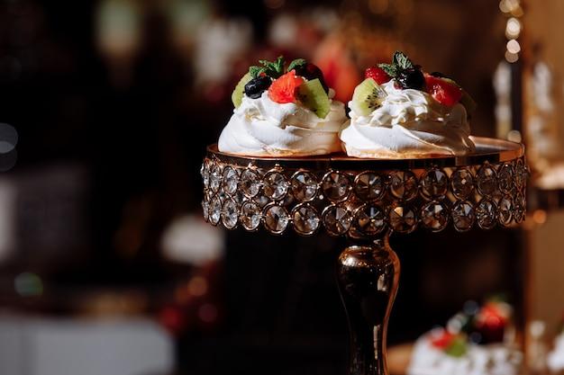 Sahne desserts mit beeren auf schokoriegel. tisch mit süßigkeiten und leckereien für den hochzeits- oder geburtstagsfeierempfang, dekoration desserttisch. leckere süßigkeiten am süßigkeitenbuffet. selektiver fokus
