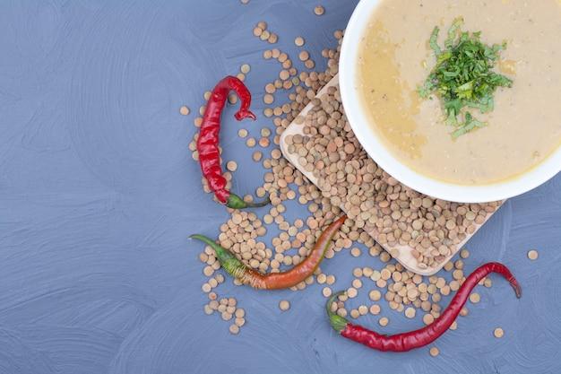 Sahne linsensuppe mit ungekochten bohnen und chilischoten herum