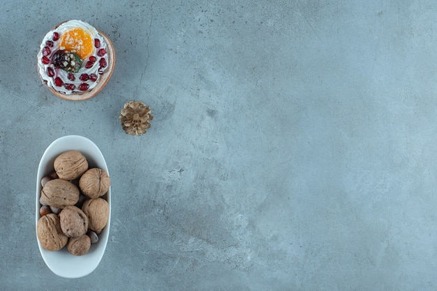 Sahne-obst-kuchen und eine schüssel mit verschiedenen nüssen auf marmoroberfläche