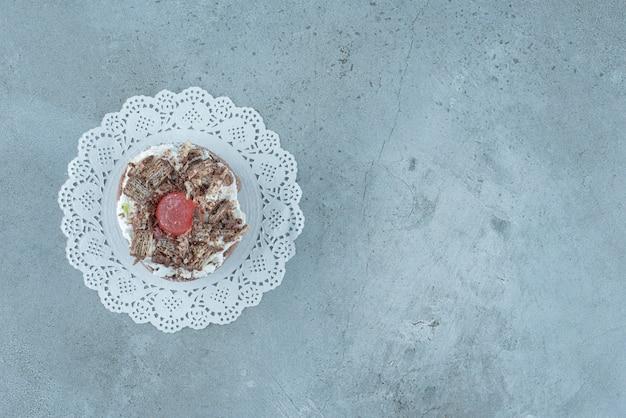 Sahne und marmelade überstiegen kuchen auf einem deckchen auf marmorhintergrund. hochwertiges foto