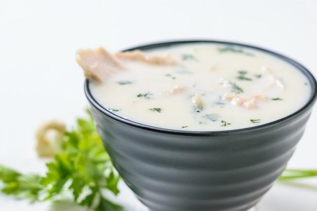 Sahneblumenkohlsuppe in einer schwarzen schüssel mit der gekochten hühnerbrust auf weißer tabelle.