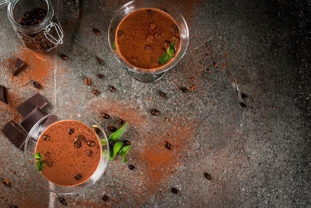 Sahnekaffeecocktail, schokoladenmartini mit minze auf schwarzer steintabelle, copyspace draufsicht