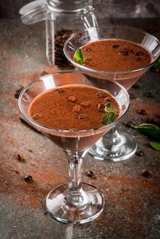 Sahnekaffeecocktail, schokoladenmartini mit minze auf schwarzer steintabelle, copyspace