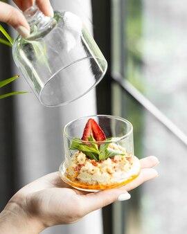 Sahnenachtisch innerhalb des glasgefäßes mit minze und erdbeere.