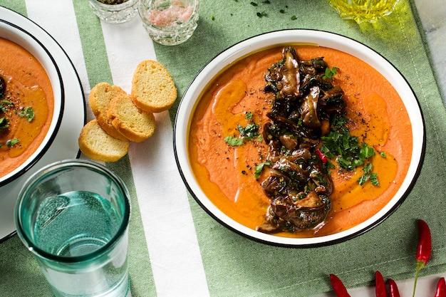 Sahnesuppe aus roten linsen mit tomaten und gebratenen waldpilzen auf dem tisch. gesundes veganes wärmendes essen für die ganze familie