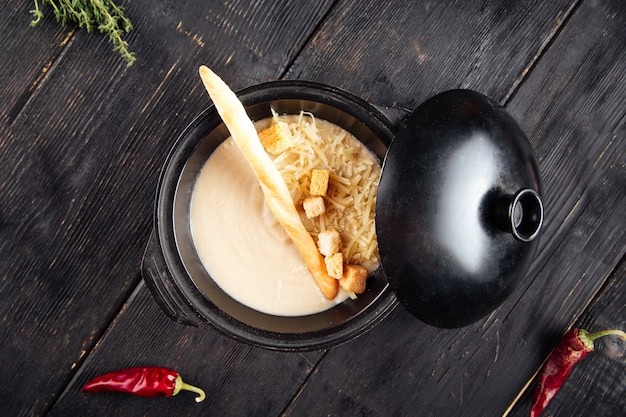 Sahnesuppe mit crackern und geriebenem käse in einer gusseisernen schüssel auf dem schwarzen holz