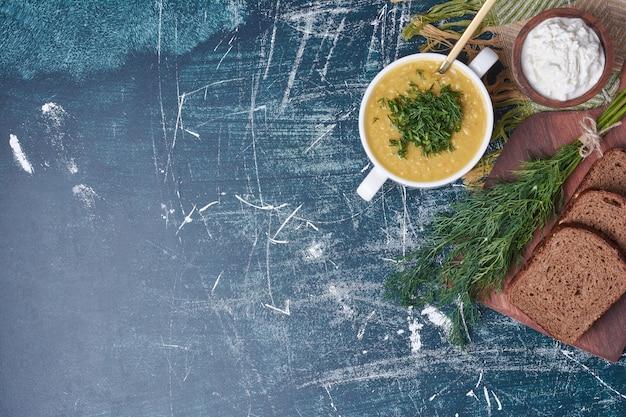 Sahnesuppe mit kräutern, sauerrahm und dunklem brot.