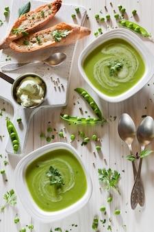 Sahnesuppe von frischen grünen erbsen mit würziger soße und getrocknetem weißbrot
