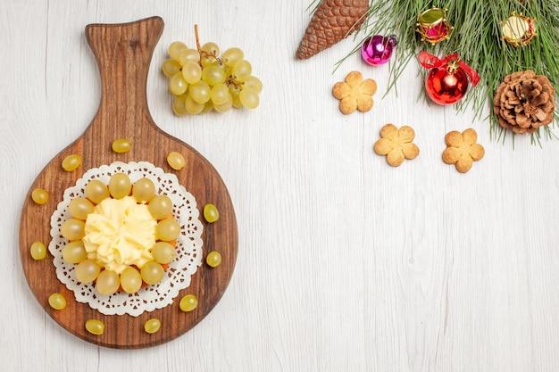 Sahnetorte von oben mit frischen trauben auf weißem schreibtisch obstkekskuchen kekskuchen