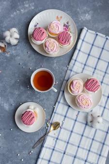 Sahnetorten in einer platte, eine tasse tee auf einem grauen marmortisch frühstück