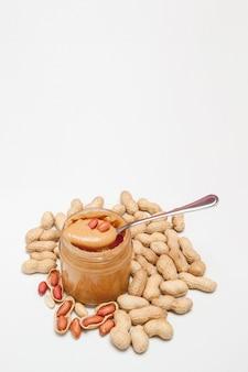 Sahnige erdnussbutter im glasgefäß, in erdnuss und in löffel lokalisiert auf weißem hintergrund. ein traditionelles produkt der amerikanischen küche