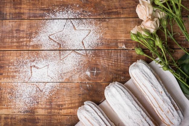 Sahnige gebackene eclairs mit rosa rosen mit den sternen gezeichnet auf zuckerpulver über dem hölzernen schreibtisch