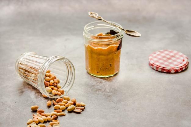 Sahnige und glatte erdnussbutter im glas auf grauer tabelle.