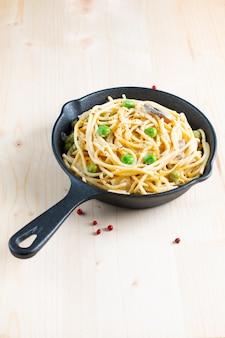 Sahnige weiße soße der lebensmittelkonzept-spaghettis in der gusseisenbratpfanne auf hölzernem hintergrund