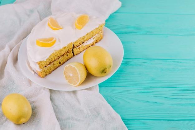 Sahniger zitronenkuchen in der weißen platte mit zitronen auf holztisch