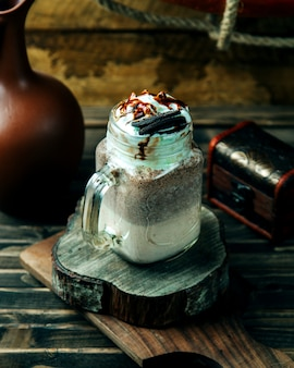 Sahniges kaffeegetränk überstiegen mit plätzchen
