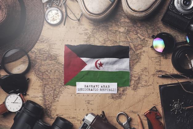 Sahrawi-flagge zwischen dem zubehör des reisenden auf alter weinlese-karte. obenliegender schuss