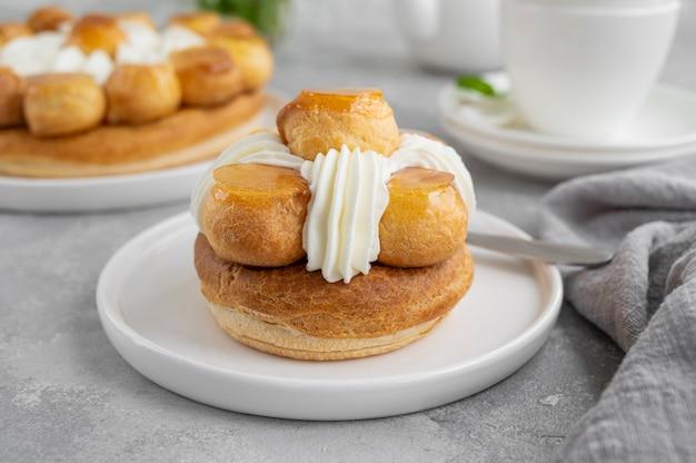 Saint honore kuchen mit profitrols, karamell, vanillepudding und schlagsahne auf einem teller.
