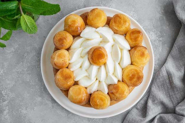 Saint honore kuchen mit profitrols karamellpudding und schlagsahne auf einem weißen teller
