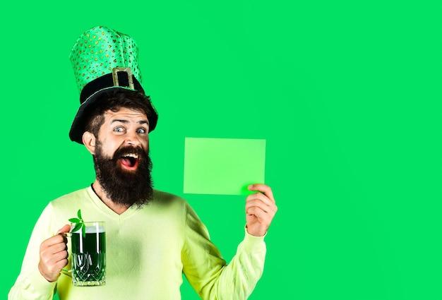 Saint patricks day symbole bärtiger mann mit grünem hut hält grünes brett st patricks day happy four