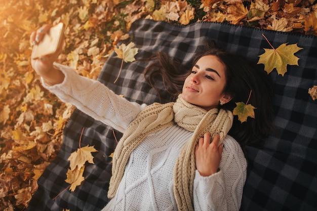 Saison-, technologie- und personenkonzept - schöne junge frau, die auf boden und herbstlaub liegt und selfie mit smartphone nimmt