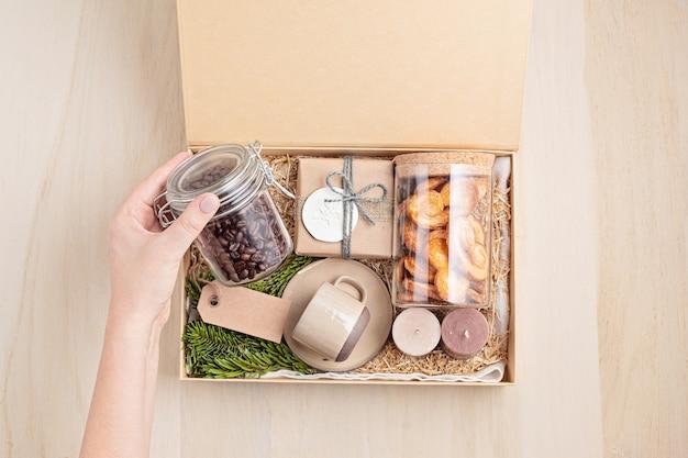 Saisonale geschenkbox mit kaffee, keksen, kerzen und tasse