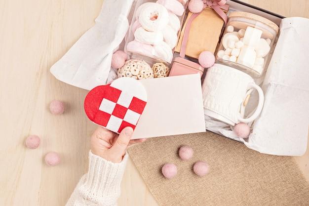 Saisonale geschenkbox mit marshmallow, kaffee und weihnachtsschmuck
