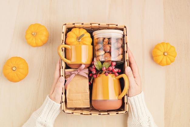 Saisonale geschenkbox mit tasse, tee oder kaffee mit keksen